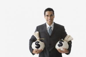 Hispanic businessman holding bags on money