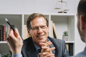 portrait-of-smiling-mature-lawyer-sitting-with-business-customer-holding-pen_23-2147898444