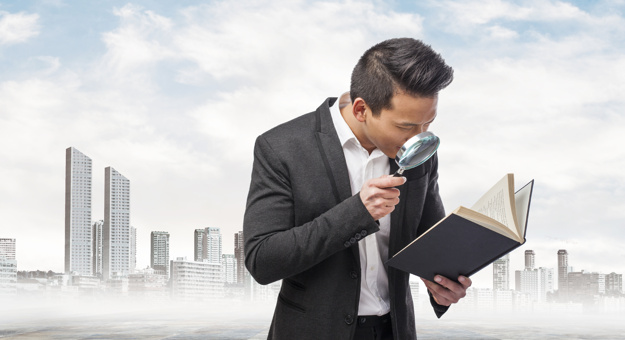 young asian business man looking through a magnifying glass
